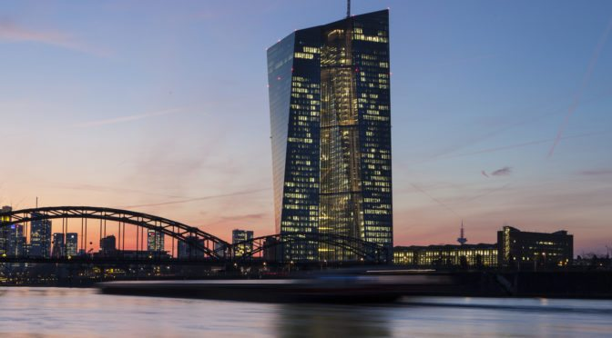 European Central Bank with the skyline of Frankfurt, Germany - in the foreground a cargo ship passing by, long exposure